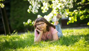Girl laying in grass with flowers